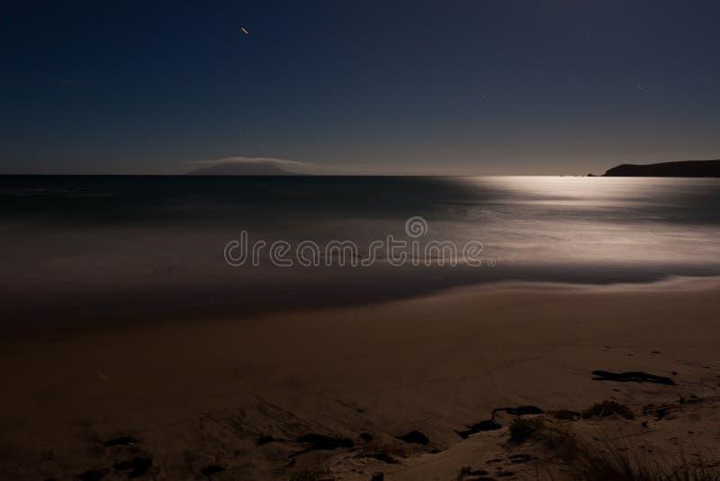 sand för romantiker för ocesn för månsken för strandexponering lång arkivfoto