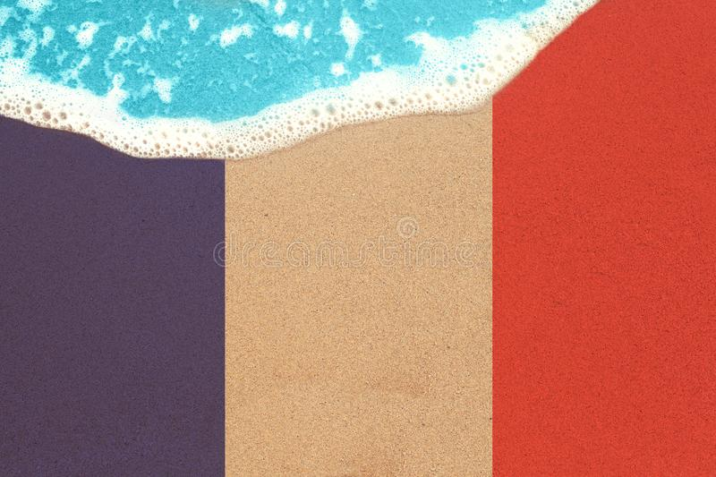 Sand with flag France and surf. Vacation on ocean beach, summer holiday stock image
