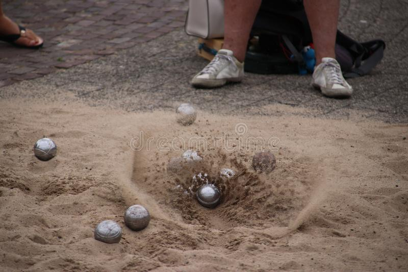 Sand is flying away when ball is landing on the ground during boules game.  royalty free stock images