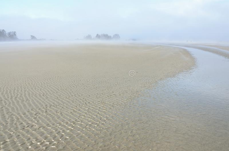 Sand forms waves on the seashore in the ocean mist, royalty free stock photos
