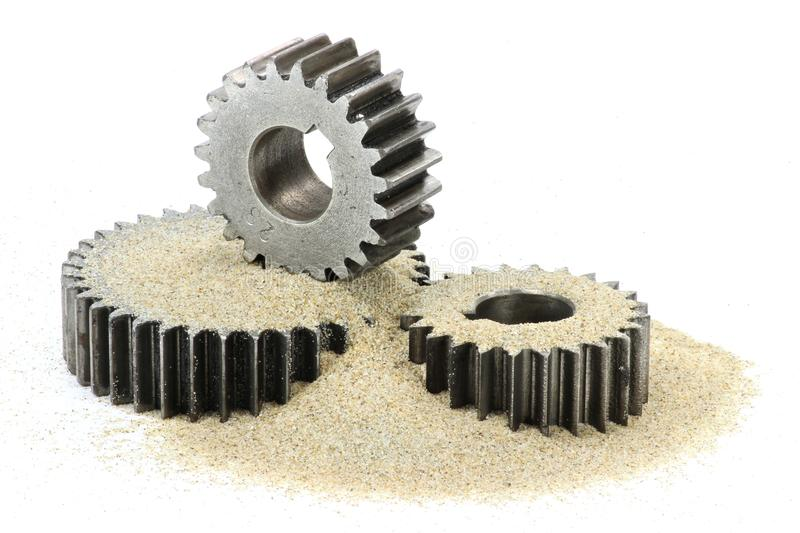 Sand in the gears. Cogs with sand isolated on white background royalty free stock photo