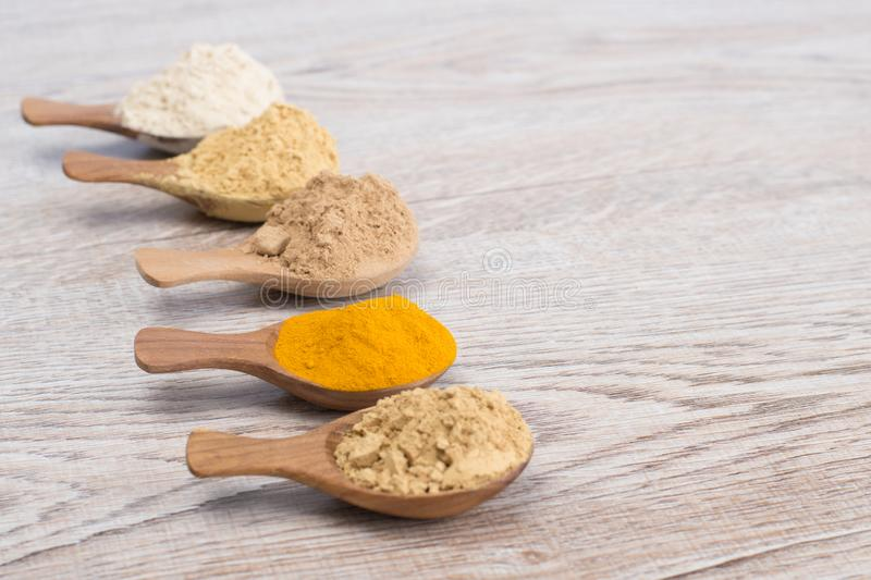 Sand ginger Kaempferia galanga, Indian Gooseberry, Turmeric ,. Tanaka , Artocarpus lacucha powder herb in wooden spoon on wooden background royalty free stock photo