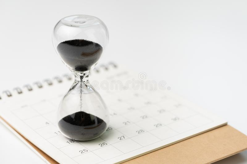 Sand glass or hour glass on white clean desktop calendar with white background and copy space using as time passing, year change. Or deadline concept stock image