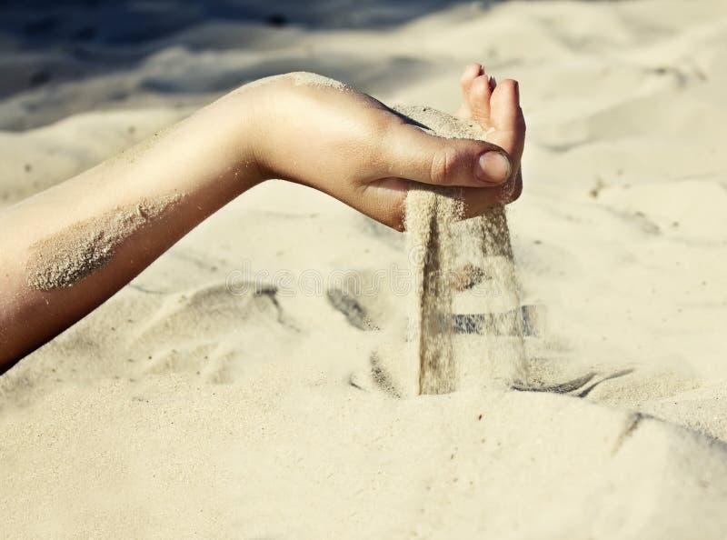 Sand häller till och med hans fingrar royaltyfri foto