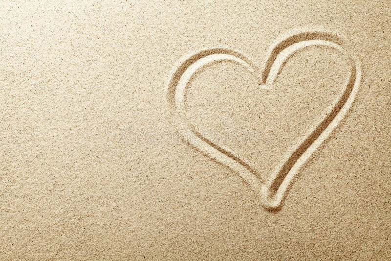 Sand Heart. Heart drawn in the sand. Beach background. Top view stock image