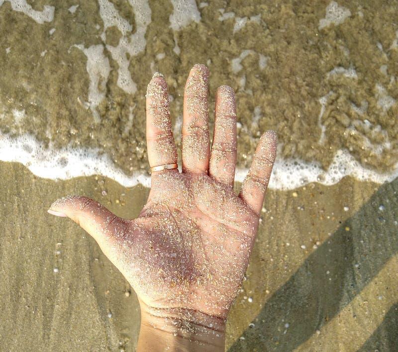 Sand kysst hand arkivbild