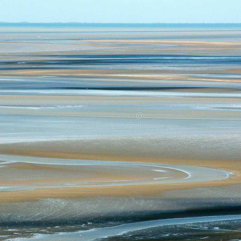 Sand at low tide. The sandy bay of Mont Saint-Michel (France) at low tide creates abstract patters of blue and sandy colours royalty free stock photo
