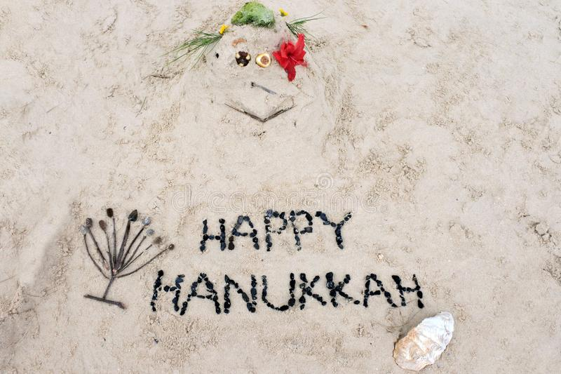 Sand man with Happy Hanukkah sign on the beach. Funny sand man with Happy Hanukkah sign on the beach.Travel, holidays and vacation concept backgrounds stock photos