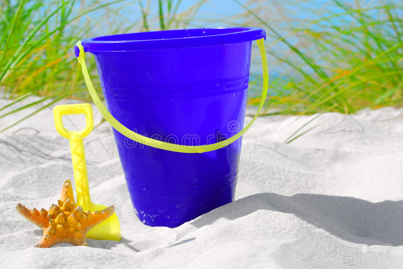 Sand pail and starfish. On beach sand stock photography
