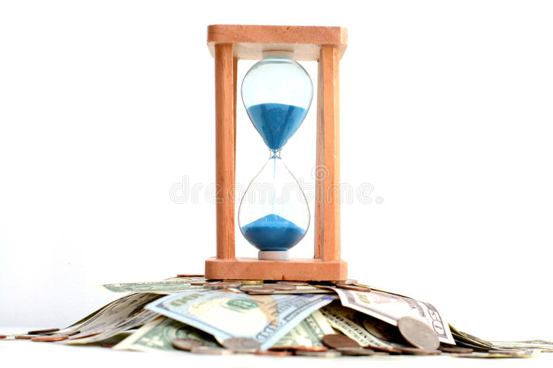 Sand pouring on hourglass standing on pile of money, suggesting deadline concept royalty free stock photos
