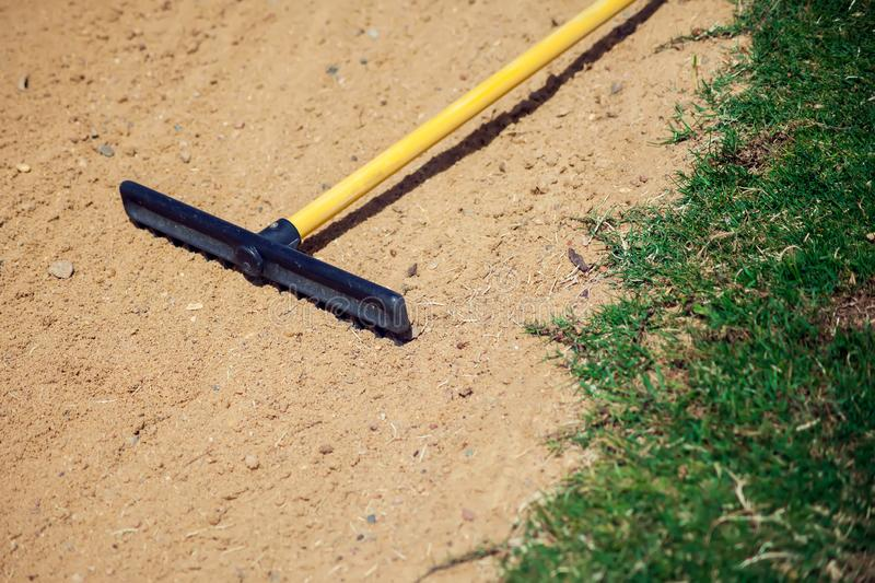 Sand rake equipment on the golf field. Sport and lifestyle concept royalty free stock images