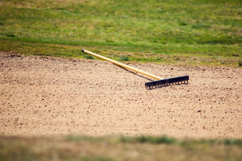 Sand rake equipment on the golf field. Sport and lifestyle concept stock photography