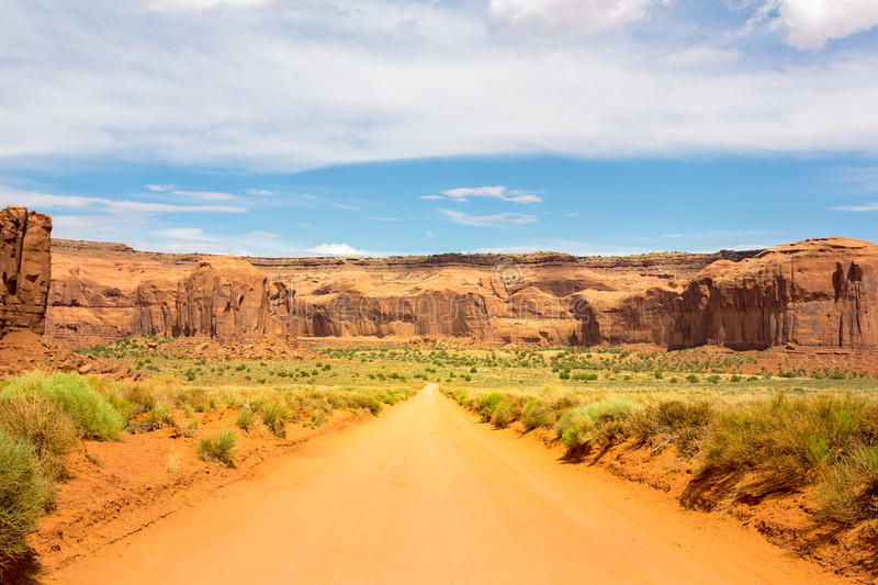 Sand road along red sandstones at Monument Valley stock images