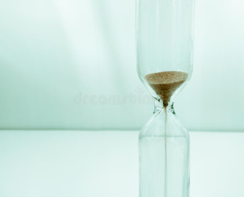 Sand running through the bulbs of an hourglass measuring the passing time in a countdown stock photo