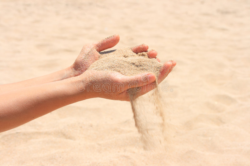 Sand running through hands stock images