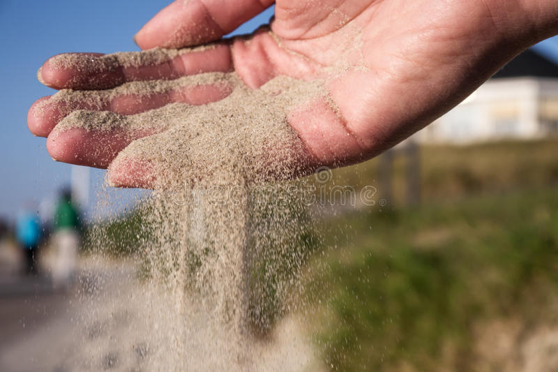 Sand running through hands. On beach stock photo