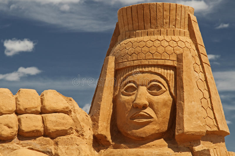 Sand sculpture aztec man head. Sand sculpture: aztec or maya stylized man head with cloudy sky as a background royalty free stock photography