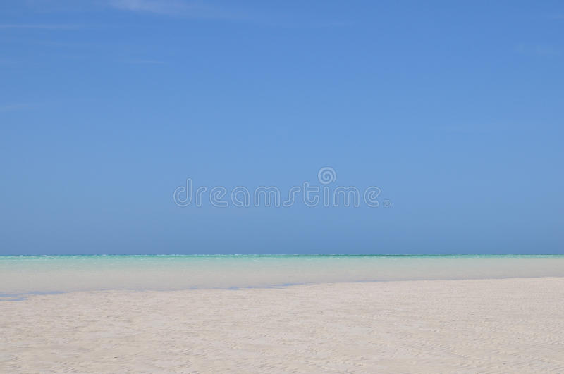 Sand, Sea & Sky. Blue sky, white sand beach and shallow water on Medjumbe Island, Mozambique royalty free stock image