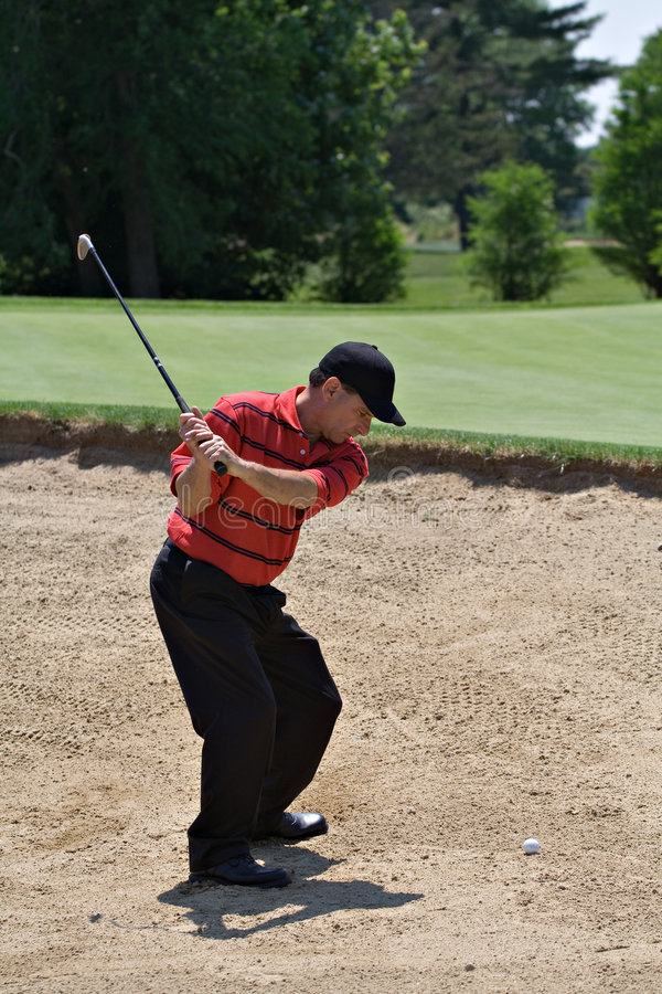 Sand Shot. Well-dressed male golfer in back swing for shot out of sand trap stock images