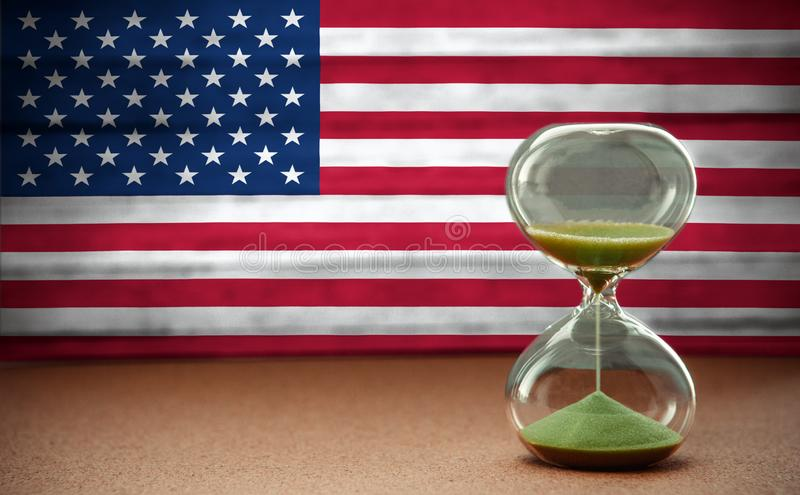 Sand som kör till och med kulorna av ett timglas som mäter den övergående tiden i en nedräkning till en stopptid, på USA flaggaba arkivbilder