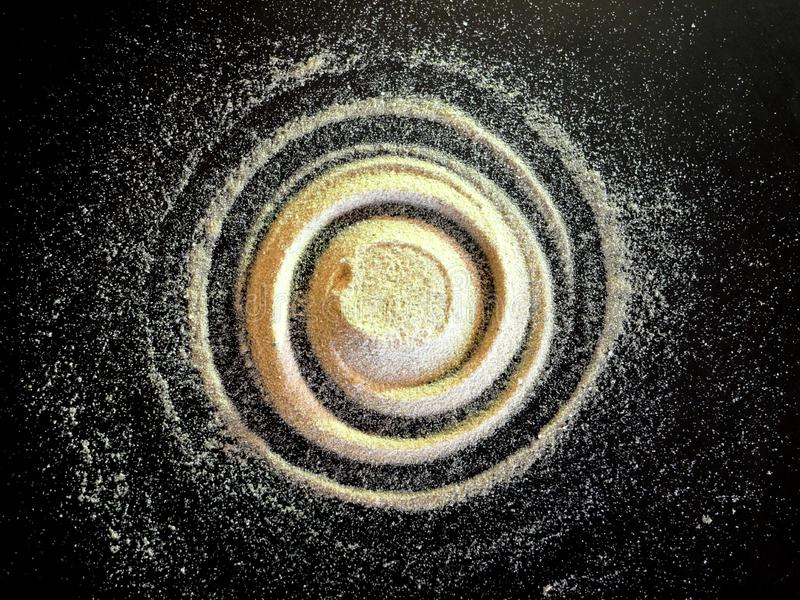 Sand spiral on the black background. The concept of rotation, golden ratio, galaxy stock photos