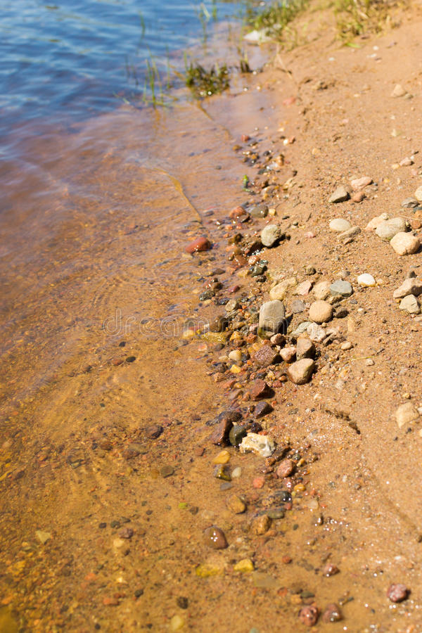 Sand and stone in river water on the beach royalty free stock image