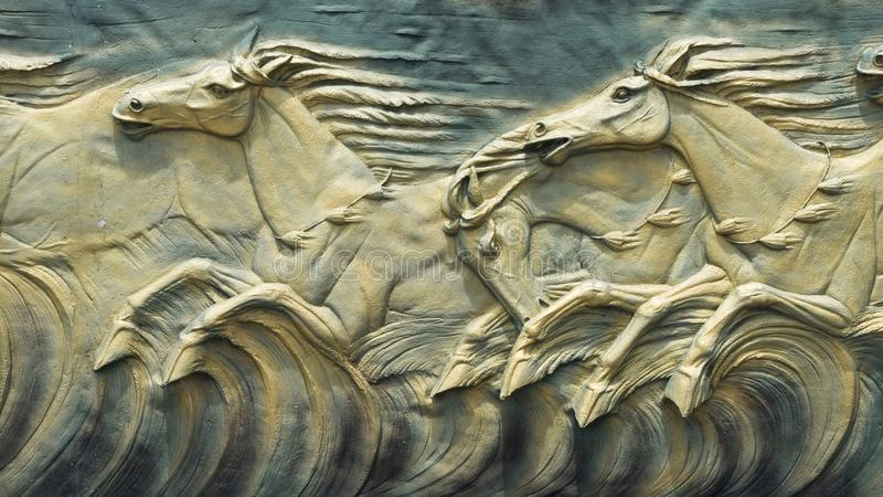 Sand stone sculpture brick green wall of herd horse run background, stock photo