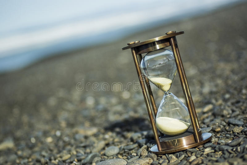 Sand-Timer auf Pebble Beach lizenzfreie stockbilder