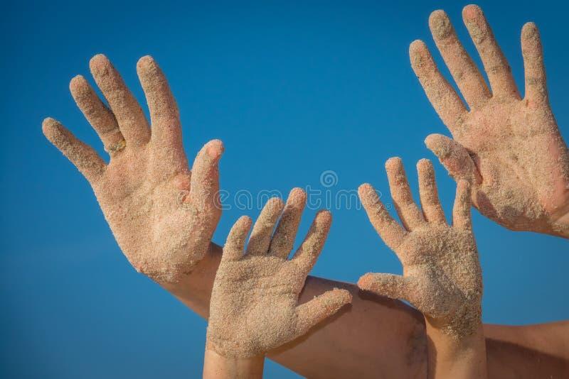 Sand umfasste Hände der Mutter und der Tochter stockbilder