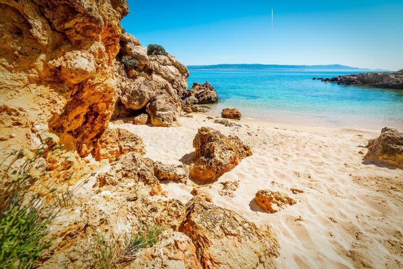 Sand und Felsen in einer kleinen Bucht von Alghero lizenzfreies stockbild