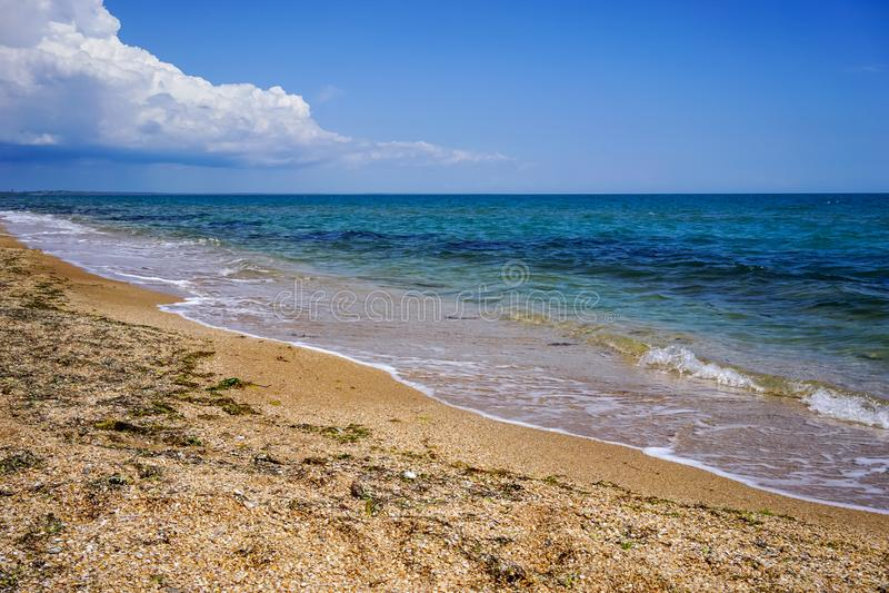 Sand und Oberteilstrand des Meeres in der Krim auf dem Hintergrund von hellem blauem Meer und von klarem Himmel lizenzfreie stockfotos
