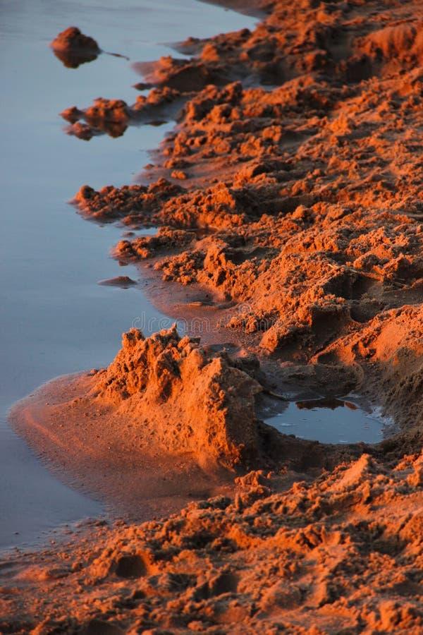 Sand vid floden p? solnedg?ngen royaltyfria foton