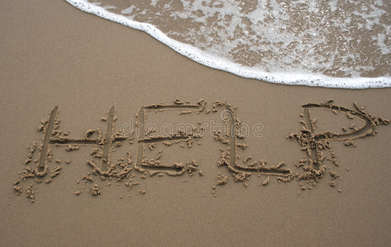 Sand writing - HELP 2. The word Help written in sand next to the shore with a wave washing over royalty free stock images