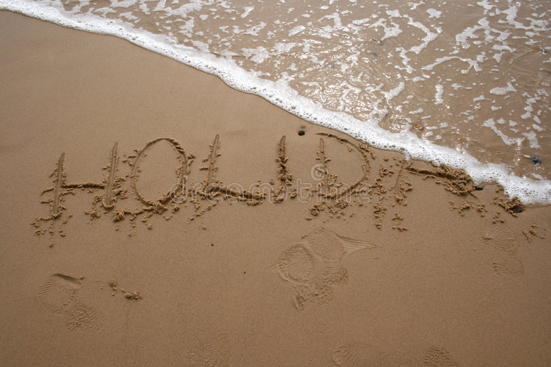 Sand writing - HOLIDAY 2. The word HOLIDAY written in sand next to the shore with a wave washing over stock photography