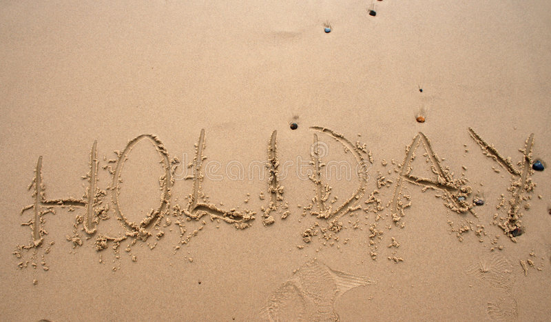 Sand writing - Holoday. The word Holiday written in sand next to the shore stock photography