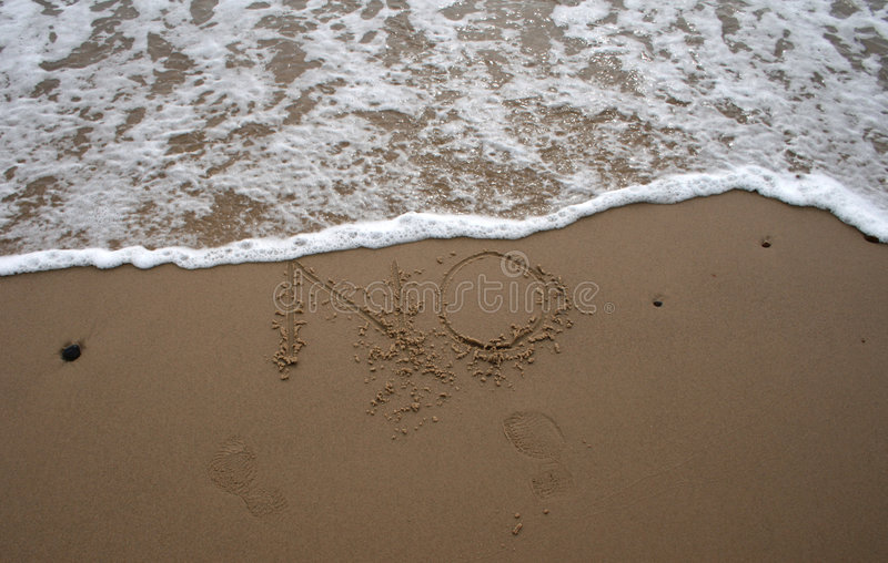 Sand writing - NO 2. The word No written in sand next to the shore with a wave washing over royalty free stock photography