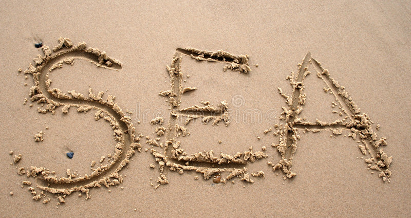 Sand writing - SEA. The word SEA written in sand next to the shore royalty free stock images