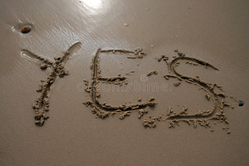 Sand writing - Yes. The word YES written in sand next to the shore royalty free stock image