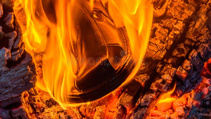 Sandal in the fire. Thsi summer is so hot - your shoes could catch fire royalty free stock image