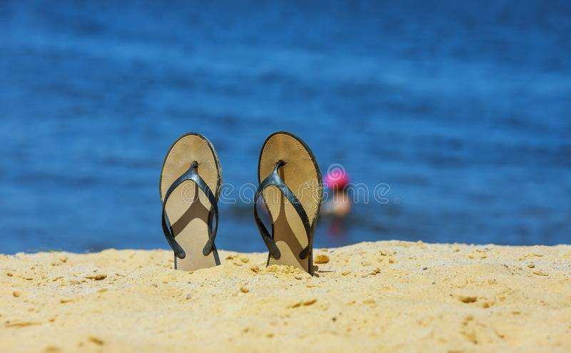Sandal flip flop on the white sand beach with blue ocean background in vacations royalty free stock image