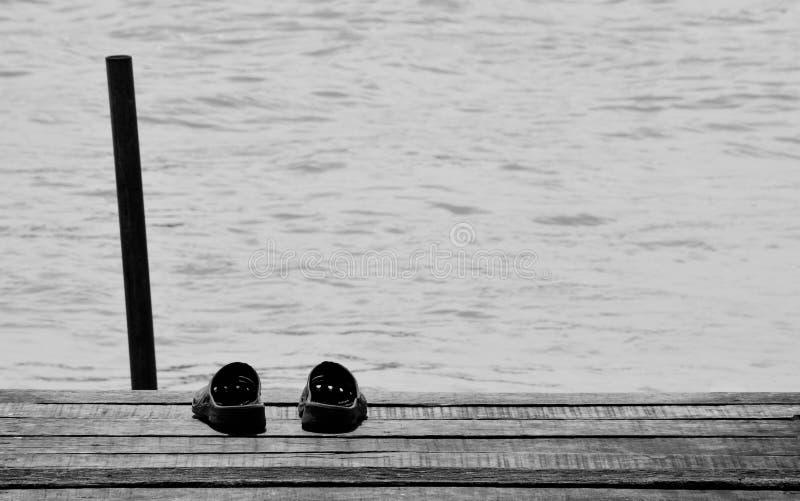 Sandal på den gamla trähamnen till sjöss royaltyfri bild