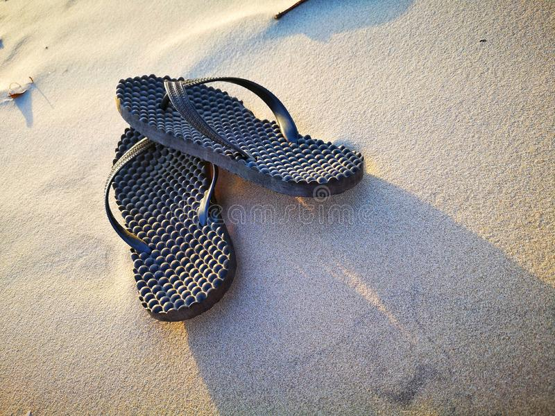 Sandal på stranden under solnedgången royaltyfri foto