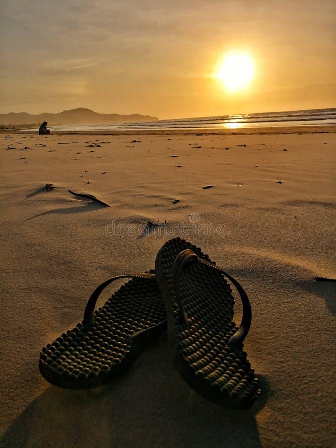 Sandal på stranden under solnedgången royaltyfri fotografi