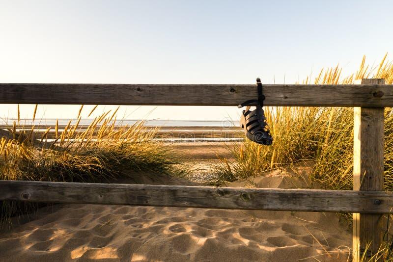 Sandal som är fäst till ett trästaket av dess rem som fångar solljuset för sen afton arkivbild