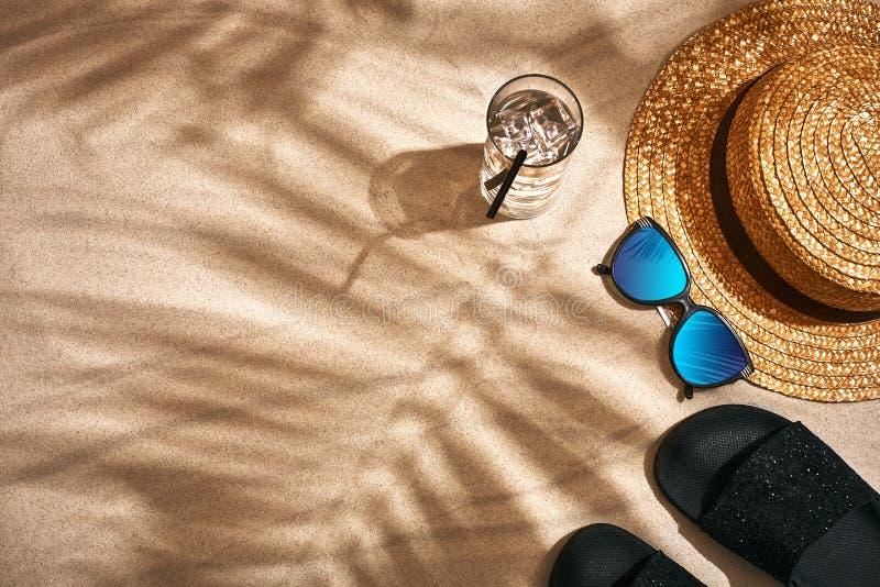 Sandale, Strohhut und Sonnenbrille auf einem sandigen Hintergrund, Draufsicht stockbilder