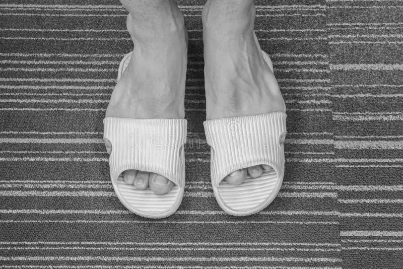 Sandale trop serrée noire et blanche de vêtements pour hommes sur ses pieds dans la maison photographie stock libre de droits