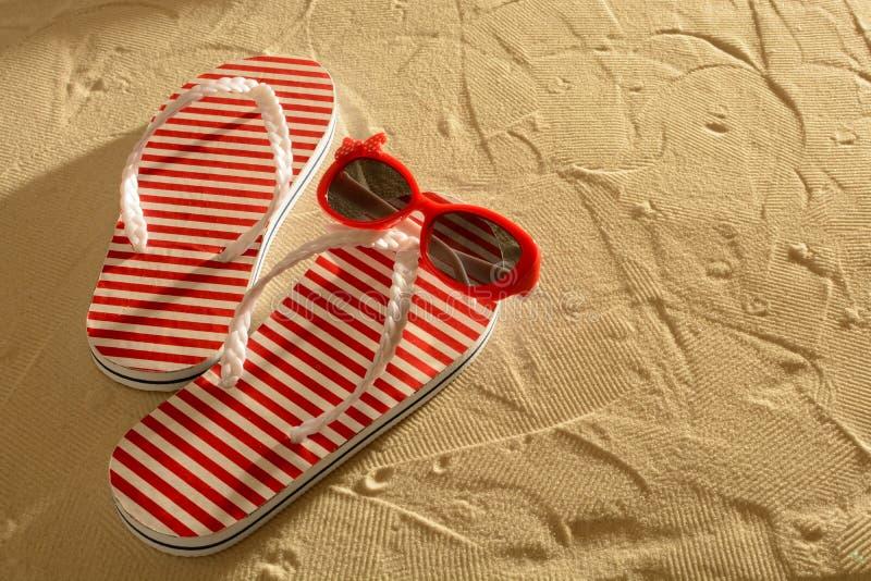 Sandale und Sonnenbrille auf einem sandigen Strand, Sonnenuntergang, Draufsicht lizenzfreie stockfotografie