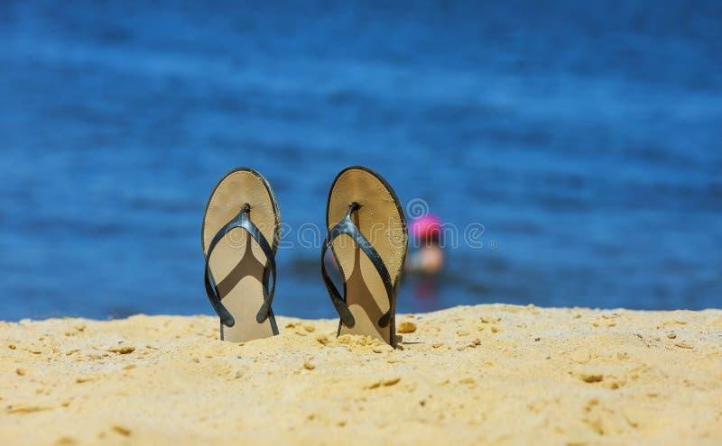 SandaleFlipflop auf dem weißen Sandstrand mit blauem Ozeanhintergrund in Ferien lizenzfreies stockbild