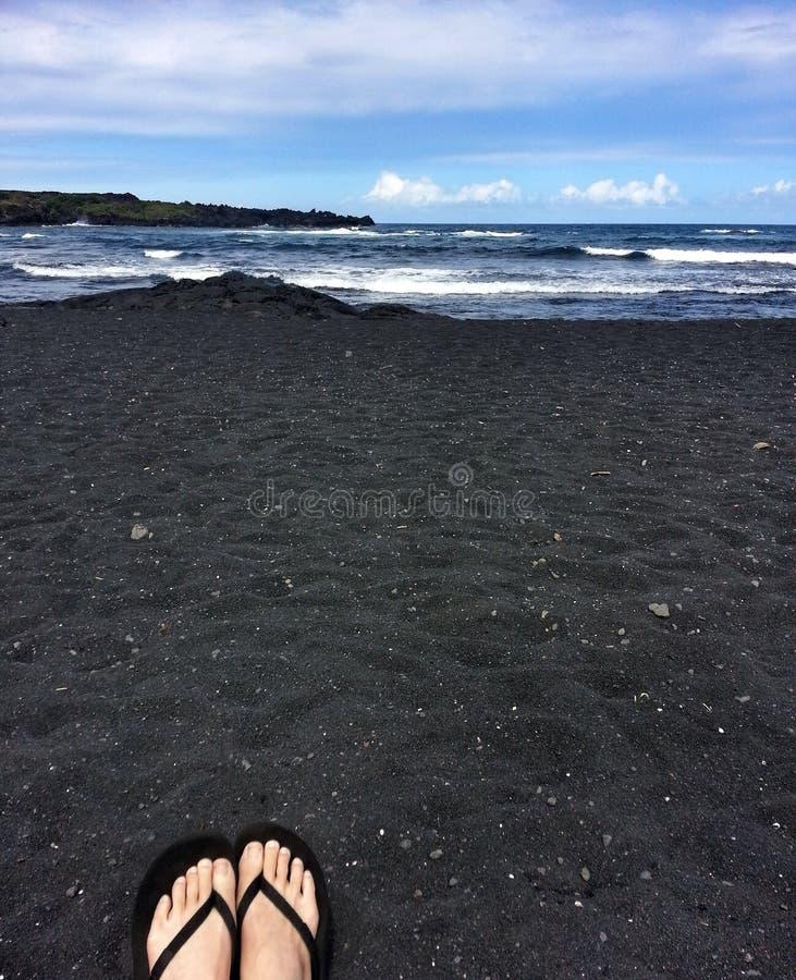 Sandalen auf schwarzem Sand-Strand, Hawaii lizenzfreie stockfotos