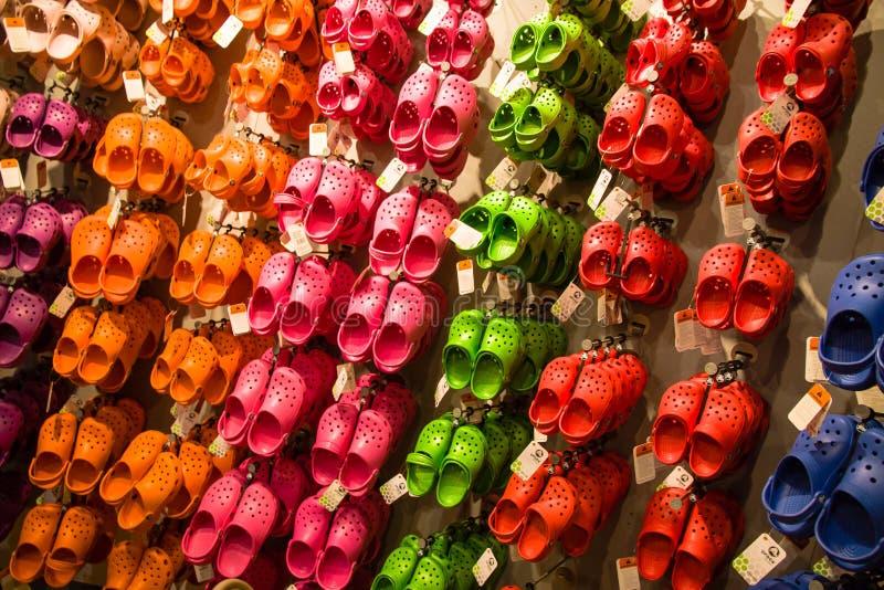 Sandaler för Crocs mjuka gummibarn som hänger på en till salu kuggeskärm Färgglade sandaler av blåa olika färger, rött, rosa, grö royaltyfri bild